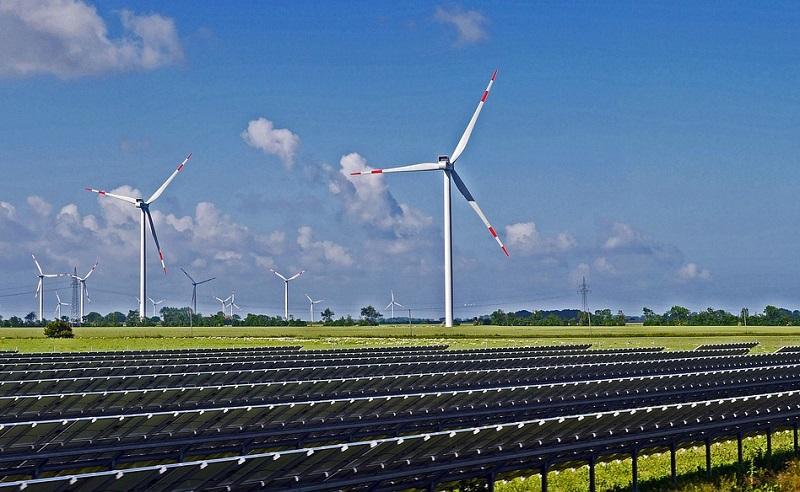 Windräder vor blauem Himmel, im Vordergrund Solaranlagen auf einem Feld