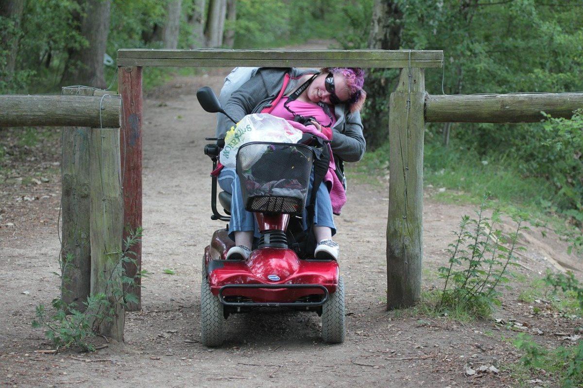 Frau im Rollstuhl fährt unter einer Absperrung durch