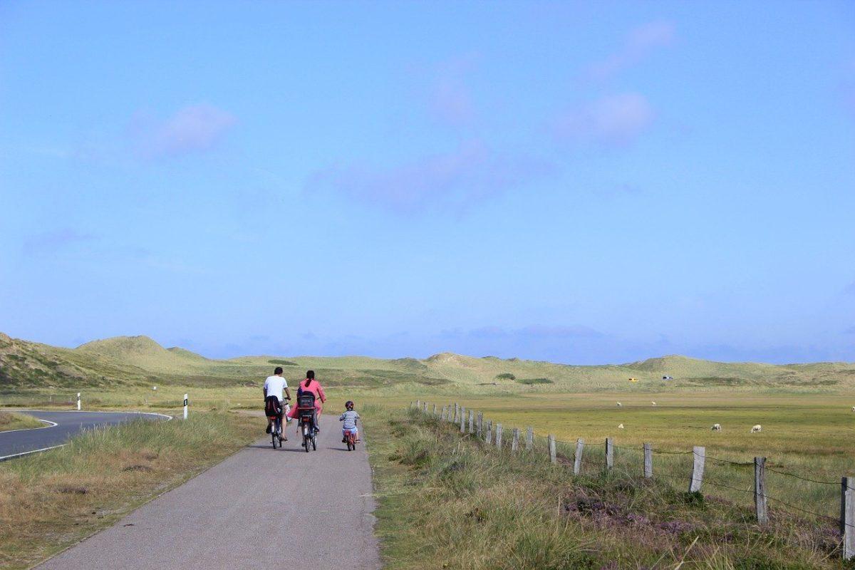 Familie auf Rädern auf einem Radweg an der Straße in Dünenlandschaft