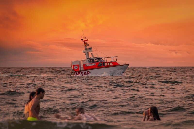 Badende und dahinter ein Rettungsboot auf dem Meer vor rotem Himmel